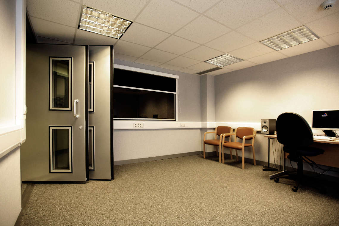 large audiometric sound room with two doors and window to the control room