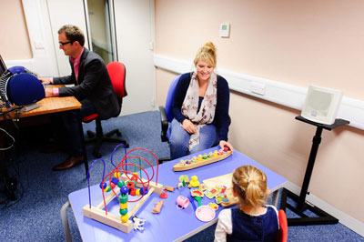 woman and man examine child's hearing in audiometric sound room