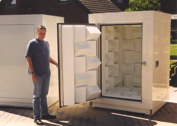 man opens the door to mini anechoic chamber in white colour